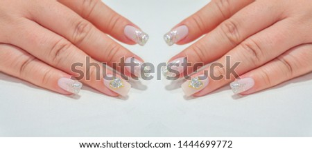 Selective Focus of Beautiful Sparkling Silver Glitter Painting on Light Pink Color Gel Polish Ombre Design Decorated with Shiny Golden Heart Shape on Ring Finger,Fahionista Woman Short Fingernail
