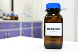 Selective focus of benzene liquid chemical compound in dark glass bottle inside a chemistry laboratory with copy space. Aromatic hydrocarbon used in petrochemical industry.