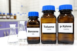 Selective focus of benzene, toluene and xylene liquid chemical compound in glass amber bottle inside a chemistry laboratory with copy space. BTX aromatic hydrocarbons used in petrochemical industry.