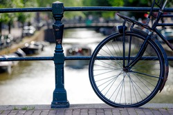 Selective focus of bicycle front wheel with blurred of canal cruise boat as background, Old vintage bike with rust parked on canal bridge in Amsterdam, Netherlands land of bicycles.