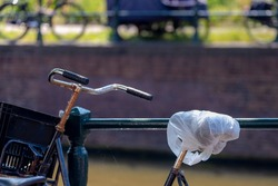 Selective focus of bicycle seat sheath with plastic bag to protected from rain or water, Typical Dutch, Amsterdam, Netherlands land of bicycles, Cycling is a common mode of transport in the Holland.