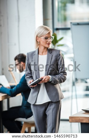 selective focus of blonde businesswoman in glasses holding notebook near coworker in office