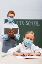 selective focus of bored schoolgirl in protective mask looking at camera, and teacher standing near chalkboard with back to school lettering