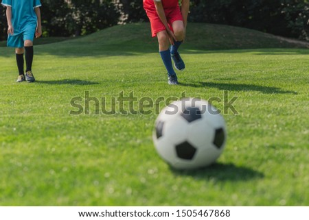 selective focus of boy touching leg near friend near football  #1505467868