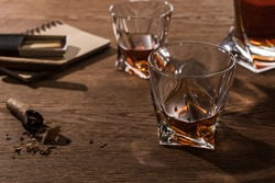 Selective focus of brandy in glasses with cigars, lighter and matches on wooden table,stock photo