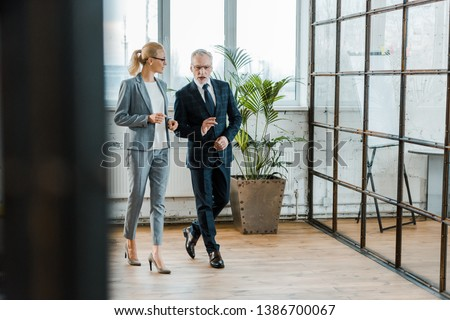 selective focus of businessman and businesswoman in eye glasses walking in office  #1386700067