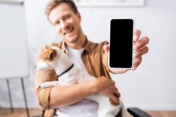 selective focus of businessman showing smartphone with blank screen while holding jack russell terrier dog
