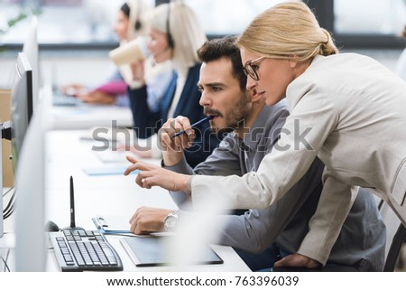 selective focus of businesswoman helping focused colleague with work at workplace in office #763396039