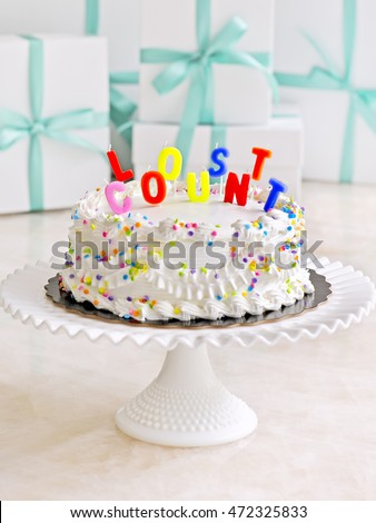 Selective Focus Of Candles On A Birthday Cake Stand With Presents In The