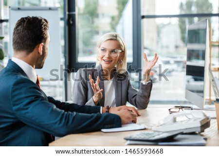 selective focus of cheerful businesswoman in glasses gesturing while looking at coworker in office