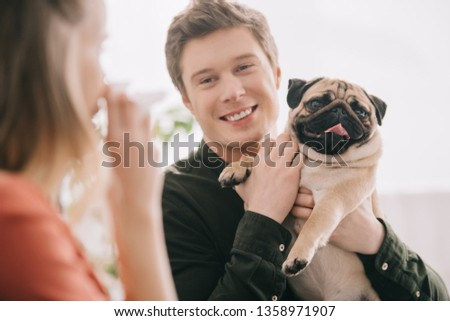 selective focus of cheerful handsome man holding pug and looking at woman allergic to dog with tissue