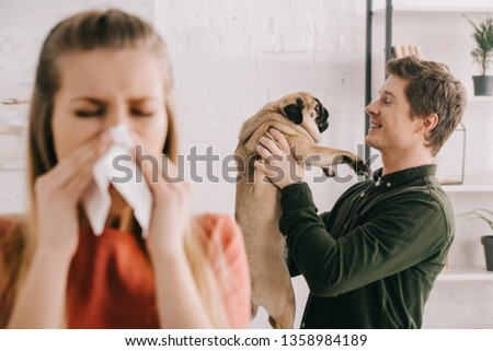 selective focus of cheerful handsome man looking at cute pug dog near woman sneezing in tissue