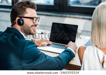selective focus of cheerful man in glasses and headset looking at blonde coworker in office