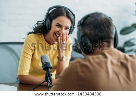 selective focus of cheerful radio host laughing while recording podcast with colleague