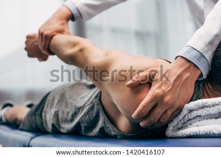 selective focus of chiropractor stretching arm of patient in hospital ストックフォト ©