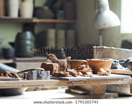 Selective focus of clay mold sculpture craft toys and pottery made by young girl. Kid activities concept. In process ceramic pieces placed on the wooden tray left to dry in sunlight. Сток-фото ©