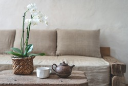Selective focus of clay teapot, white cup and orchid flower at wooden table against blurred wall with copy space on background. Cozy house with comfort sofa in vintage interior style