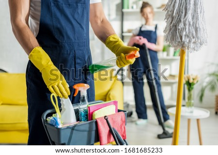 selective focus of cleaner holding spray bottle near cleaning trolley