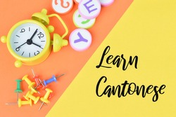 Selective focus of clock, alphabet erasers and pinboards over orange and yellow background written with  text LEARN CANTONESE.