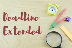 Selective focus of clock, compass geometry, memo note and magnifying glass on wooden background written with text DEADLINE EXTENDED. Business and education concept.