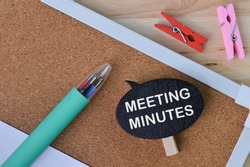 Selective focus of clothespins, brown board, pen and wooden tag written with MEETING MINUTES. A business concept.