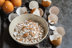 selective focus of cracked eggshells and grinded eggshells on dark stone table