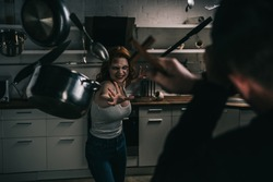 selective focus of creepy demon with levitating cookware and exorcist with cross in kitchen