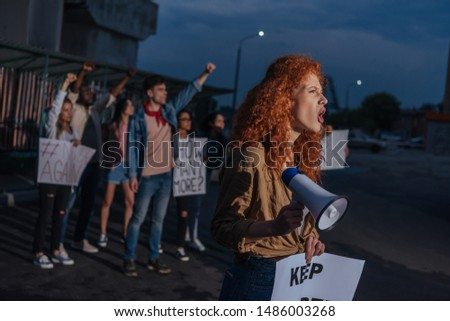 selective focus of curly redhead girl holding placard and screaming on meeting   #1486003268