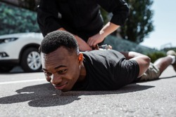selective focus of detained african american man lying on street near policeman, racism concept
