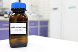 Selective focus of dichloromethane liquid chemical compound in dark glass bottle inside a chemistry laboratory with copy space.