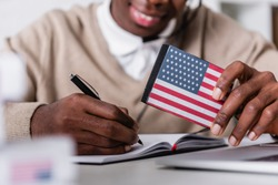 selective focus of digital translator with usa flag emblem near african american interpreter writing on blurred background, cropped view