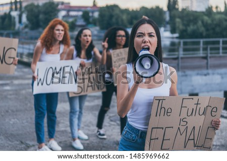 selective focus of emotional girl holding placard with the future is female letters and screaming in megaphone outside  #1485969662