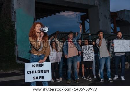 selective focus of emotional redhead girl holding placard with keep children safe lettering and screaming near multicultural people on meeting  #1485959999