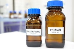 Selective focus of ethanol and methanol brown amber glass bottle inside a laboratory. Blurred background with copy space.