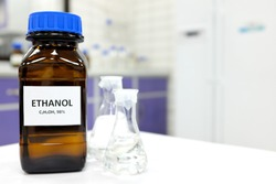 Selective focus of ethanol or ethyl alcohol in brown glass bottle inside a laboratory.