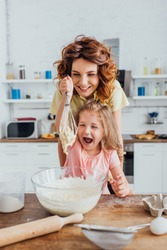 selective focus of excited girl holding whisk with dough near mother