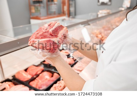 Selective focus of fresh red raw piece of meat in hands of young incognito woman. From above view of girl standing behind counter with big variety of meat and showing pork from refrigerator. Foto stock ©