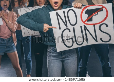 selective focus of girl pointing with finger at placard with no gun lettering near people on black  #1485971585