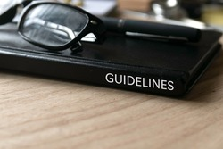 Selective focus of glasses, pen and black book title of Guidelines on wooden background.