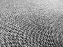 Selective focus of gray textured fabric. Macro shot of gray upholstery for furniture. Wallpaper and background. Closeup grey fabric texture. Thick gray material for the interior.