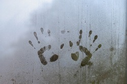 Selective focus of hand marks on glass condensation window, Two hand prints with raindrop on the window with blurred background.