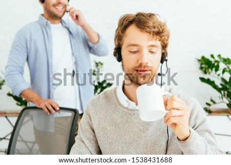 selective focus of handsome bearded broker holding cup near coworker in office