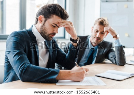 selective focus of handsome bearded businessman holding pen near document and coworker in office