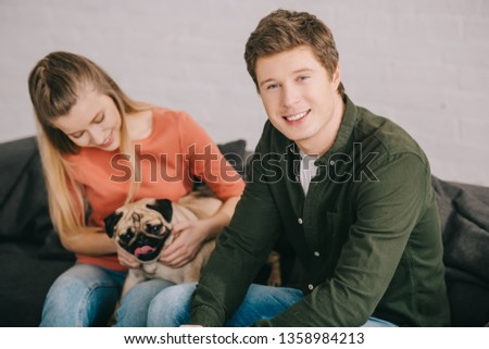 selective focus of handsome smiling man sitting near woman with adorable pug dog
