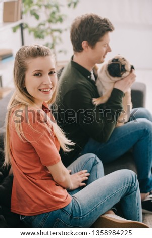 selective focus of happy blonde woman looking at camera near happy man with cute pug dog