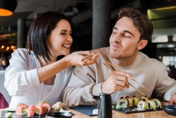 selective focus of happy woman holding chopsticks with tasty sushi near cheerful man in restaurant