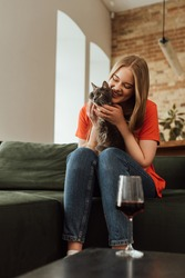selective focus of happy young woman holding cute cat near glass of red wine