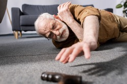 selective focus of helpless senior man fallen on floor and trying to get walking stick
