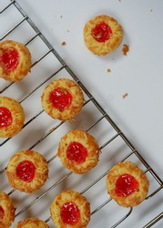 Selective focus of Homemade thumb print cookies filled with strawberry jam and grated cheese. Served for eid al fitr. Look like noised with strawberry thumbprint cookies.