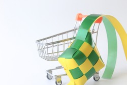selective focus of Ketupat (Rice Dumpling) with shopping trolley or pushcart isolated on white background. Ketupat is a natural rice casing made from young coconut leaves for cooking rice. Eid Mubarak